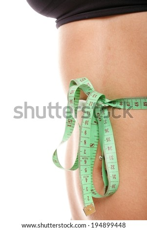 Close-up of slim stomach with measuring tape around it Woman body part is being measured