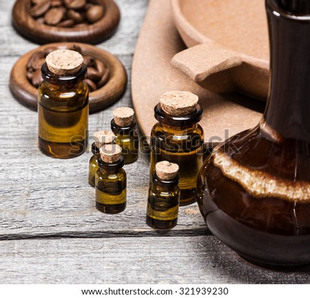 Close-up of small glass vials filled with natural aromatic essential oils next to crock, bamboo utensils with water and coffee beans on old wooden planks. Aromatherapy accessories - stock photo