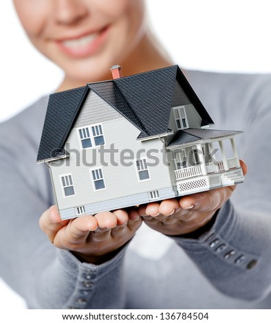 Close up of small model house in female hands, isolated on white - stock photo