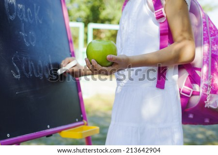 Close-up of small schoolgirl writing Back to school on blackboard, education concept - stock photo