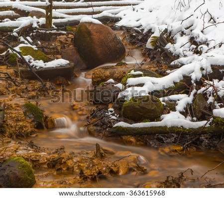 Close up of small stream in winter forest. Snow covered shore of small river. - stock photo