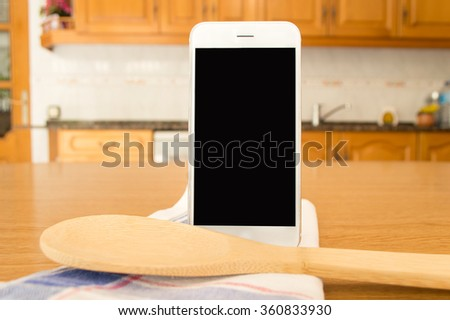 close up of smartphone on a table wooden next a cloth and wooden kitchenware - stock photo