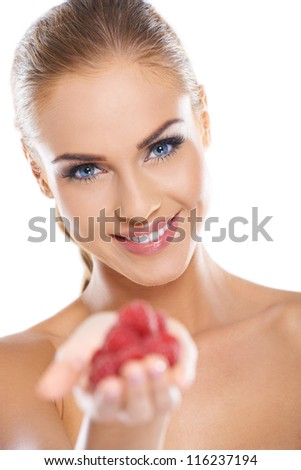 Close up of smiling blonde holding raspberries while isolated - stock photo