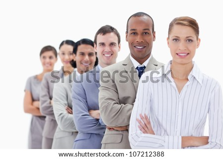 Close-up of smiling colleagues dressed in suits crossing their arms in a single line with focus on the first man - stock photo