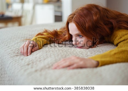 Close Up of Smiling Contented Young Woman with Red Hair Wearing Yellow Sweater Lying on Stomach on Comfortable Bed with Textured Duvet - stock photo
