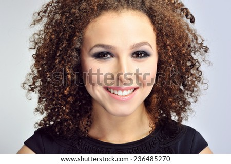 Close up of smiling curly hair woman  - stock photo