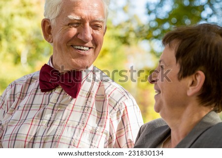 Close-up of smiling elderly man looking at his happy woman - stock photo