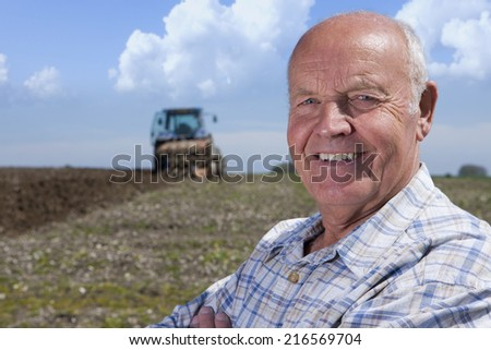 Close up of smiling farmer in field with tractor and plough in background - stock photo