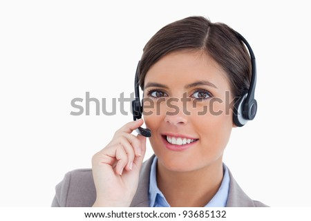 Close up of smiling female call center agent adjusting her headset against a white background