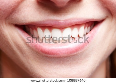 Close-up of smiling female mouth with white teeth showing - stock photo