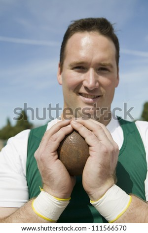 Close-up of smiling male athlete holding shot put - stock photo