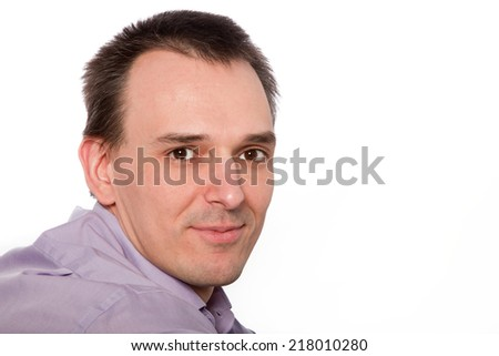 Close Up of Smiling Man Wearing Purple Shirt in Studio with Copyspace on White Background