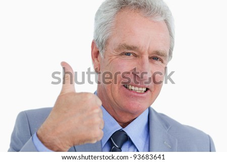 Close up of smiling mature tradesman giving thumb up against a white background - stock photo