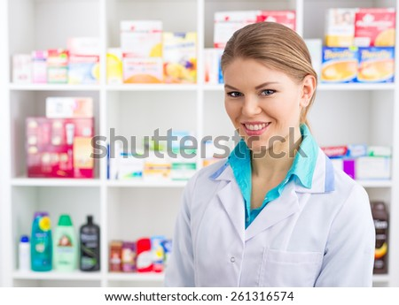 Close-up of smiling medical assistant servicing customers in drugstore. Young female intern in labcoat selling pharmaceuticals. - stock photo