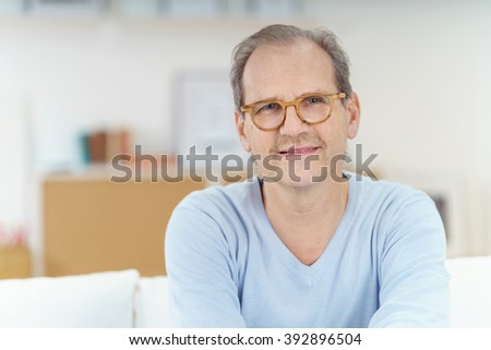 Close up of smiling middle aged man with receding hairline and mustache sitting on sofa - stock photo