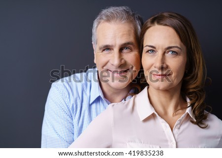 Close up of smiling older couple against a blue background and wearing business casual clothing - stock photo