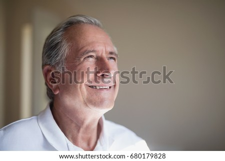Close-up of smiling senior male patient looking away at hospital ward