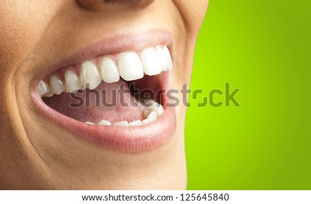 Close Up Of Smiling Teeth against a green background - stock photo