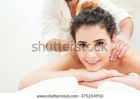 Close-up of smiling woman getting a relaxing massage as wellbeing and pamper concept - stock photo