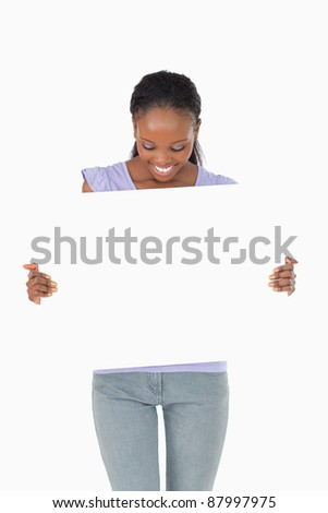 Close up of smiling woman looking at placeholder in her hands on white background - stock photo