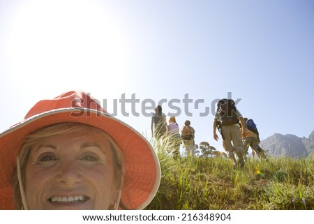 Close up of smiling woman with hikers in background - stock photo