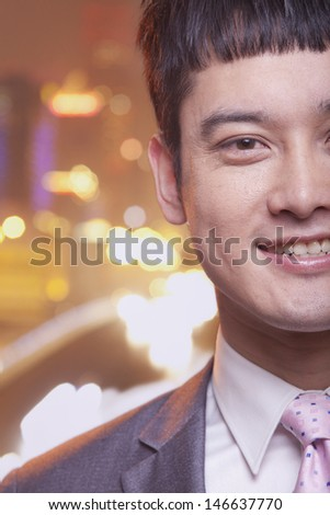 Close-up of smiling young business man, city lights background - stock photo