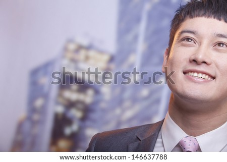 Close-up of smiling young business man looking up - stock photo