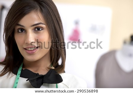 Close-up of smiling young fashion designer in clothing store - stock photo