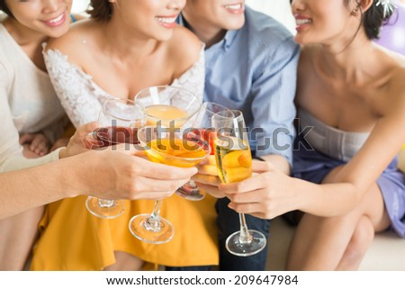 Close-up of smiling young people clinking glasses and toasting - stock photo