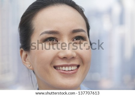 Close-up of smiling young woman looking up