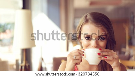 Close Up of Smiling Young Woman Sipping Coffee from White Mug in Sunny Window Seat of Trendy Cafe Restaurant with Copy Space - stock photo