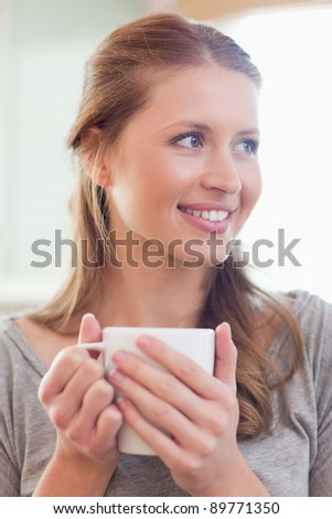 Close up of smiling young woman with a cup of tea - stock photo
