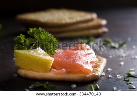 Close-up of smoked salmon served with crackers and lemon - stock photo