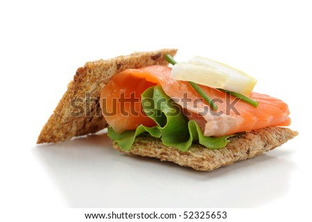 Close-up of smoked salmon served with crackers, lemon and salad