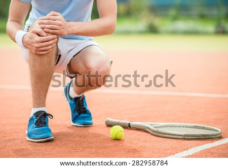 Close-up of sneakers near the tennis racquet and ball. - stock photo