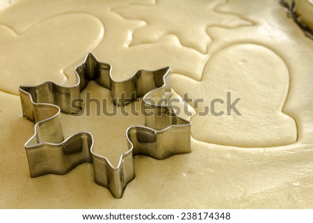 Close up of snowflake and mitten cookie cutters cutting out holiday sugar cookies