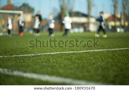 Close-up of soccer field with blurred children playing a soccer match in the background. - stock photo