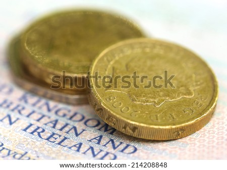 Close up of some British Pound coins on passport - stock photo