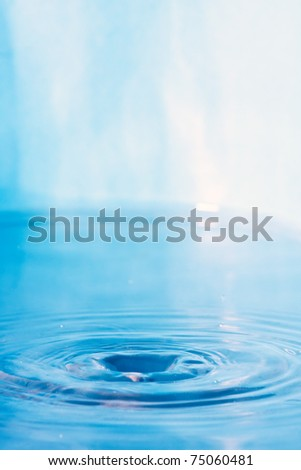 Close up of some clear blue water with circular ripples and plenty of copy space. - stock photo