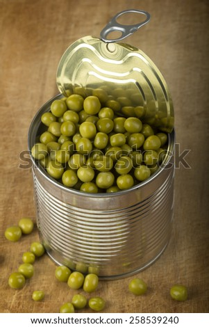 Close up of some peas in can over wood background - stock photo