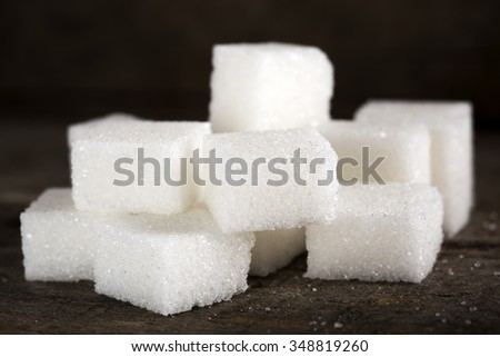 Close-up of some sugar cubes over wooden table - stock photo