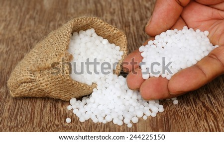 Close up of some Urea Fertilizer in sack with human hand - stock photo