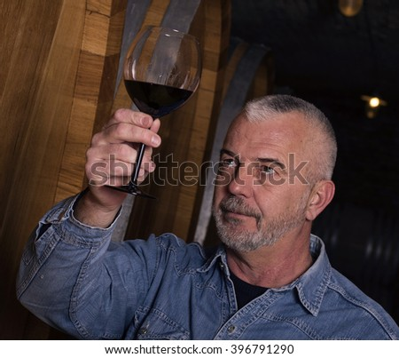 Close up of sommelier tasting wine in the wine cellar - stock photo