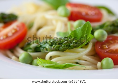 Close-up of spaghetti with asparagus and green peas - stock photo