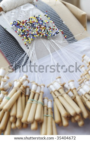 Close-up of special lace making pin cushion. Pins and wooden bobbins for lace making. Traditional craft in many countries in Europe - stock photo