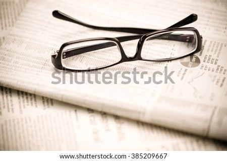 Close-up of spectacles over folded newspaper.