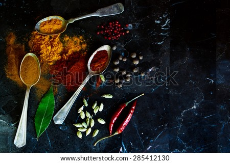 Close up of spices selection in old metal spoons on a stone background with space for text. Top view. Cooking, healthy eating. - stock photo