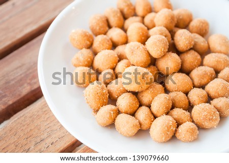 Close up of spicy peanuts snack on white dish - stock photo