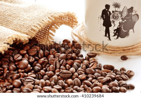 Close-up of spilled coffee beans from canvas sack and porcellaneous mug in background - stock photo