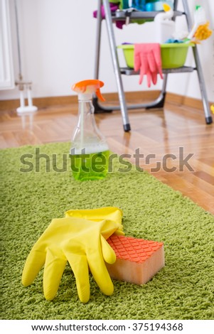 Close up of sponge and protective gloves on green carpet with cleaning supplies on ladder in background - stock photo